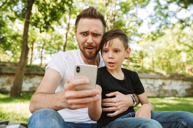Choqué jeune père assis avec son petit-fils à l'aide de téléphone portable.