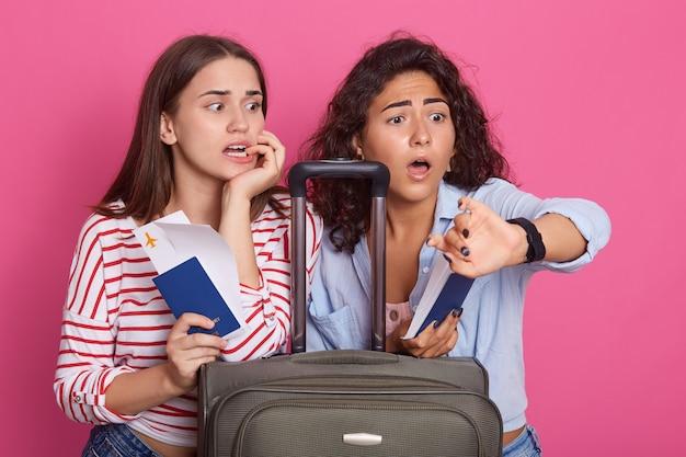 Choqué de jeunes femmes portant des tenues élégantes, étant en retard, regardant la montre avec une expression faciale effrayée, posent près de la valise
