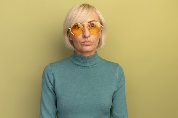 Choqué jolie blonde femme slave dans des lunettes de soleil regarde la caméra sur vert olive