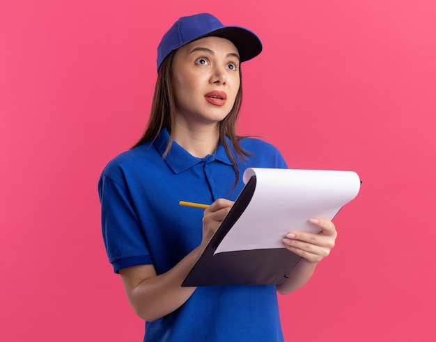 Choqué jolie femme de livraison en uniforme tient un crayon et un presse-papiers en levant isolé sur un mur rose avec copie espace