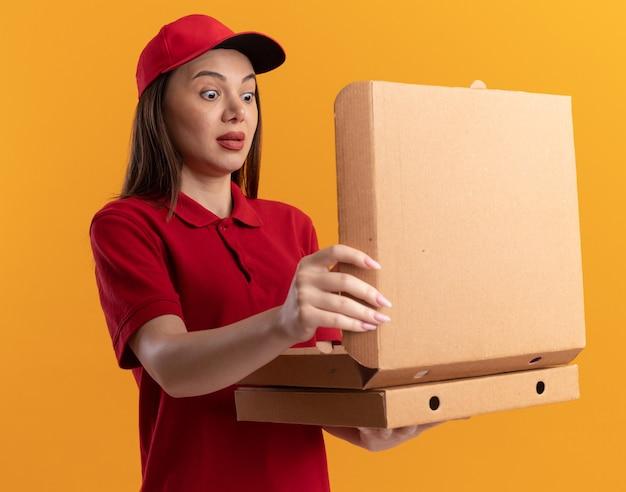 Choqué jolie femme de livraison en uniforme tient et regarde les boîtes de pizza sur orange