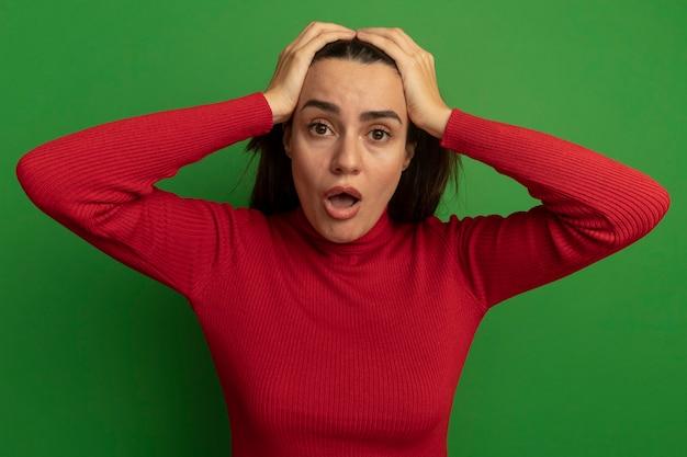 Choqué jolie femme tient la tête à deux mains isolé sur mur vert