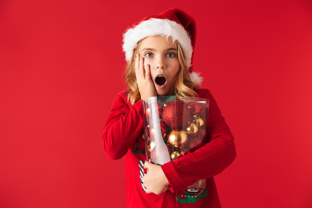 Choqué petite fille portant le costume de noël debout isolé, tenant ensemble de jouets d'arbre de noël