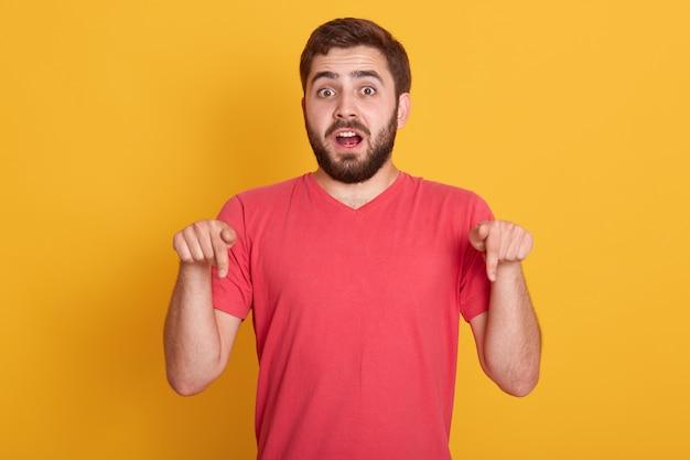 Choqué peur jeune homme ayant peur de quelque chose, pointant vers le bas avec ses doigts antérieurs, ayant surpris et étonné l'expression faciale, posant isolé sur jaune