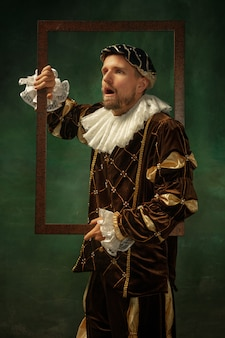 Choqué. portrait de jeune homme médiéval en vêtements vintage avec cadre en bois sur fond sombre. modèle masculin en tant que duc, prince, personne royale. concept de comparaison des époques, moderne, mode, ventes.