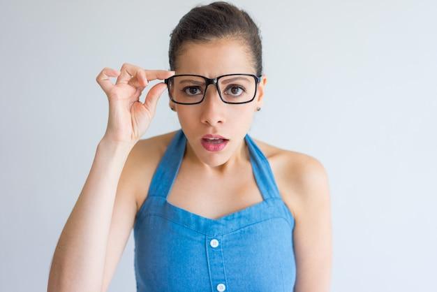 Choqué séduisante jeune femme en ajustant les lunettes et en regardant la caméra.
