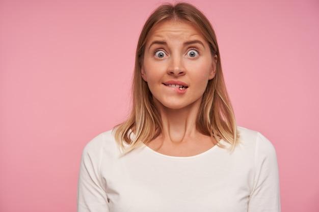 Choqué séduisante jeune femme blonde mordant la lèvre inférieure et regardant la caméra avec de grands yeux ouverts, levant les sourcils et le front plissé sur fond rose
