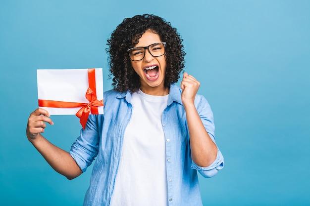 Choqué surpris jeune femme afro-américaine bouclée isolée sur fond bleu portrait en studio. maquette de l'espace de copie. tenant un certificat-cadeau.