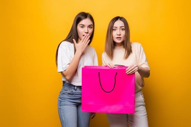Choqué surpris jeunes femmes filles amis dans des lunettes de vêtements en denim posant isolé sur un mur jaune. concept de mode de vie des émotions sincères. tenant le sac d'emballage avec les achats après le shopping