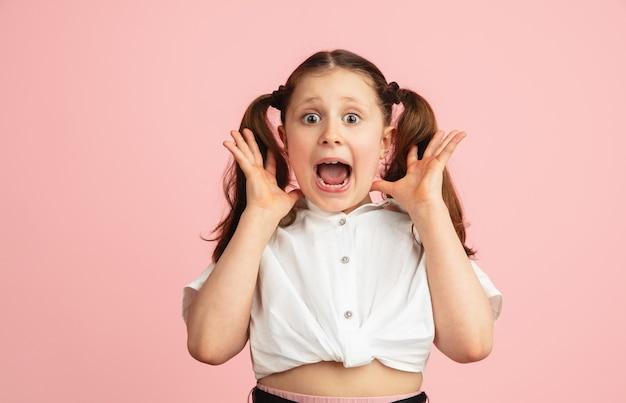 Choqué, surpris. portrait de jolie fille caucasienne isolé sur mur rose avec fond. modèle élégant à cheveux longs. concept d'émotions humaines, d'expression faciale, de mode, de jeunesse.