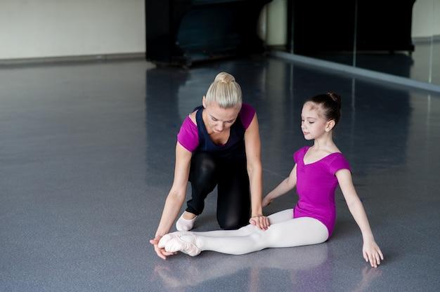 Le chorégraphe enseigne à l'enfant la bonne posture.