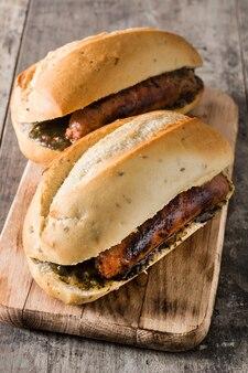 Choripan sandwich traditionnel de l'argentine au chorizo et à la sauce chimichurri sur une table en bois