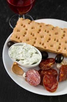 Chorizo avec du fromage, des olives et des toasts