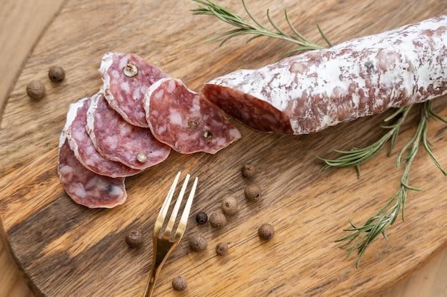 Chorizo ibérique, chorizo espagnol ou saucisse espagnole coupée en tranches sur une planche de bois avec du pain rustique