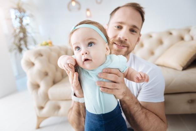 Des choses intéressantes autour de moi. curieuse jolie fille agréable debout près de son jeune père et regardant ailleurs tout en exprimant son intérêt et en faisant des pas