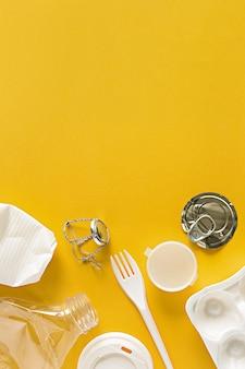 Choses en plastique brut secondaire pour la réutilisation ou le recyclage à plat sur fond jaune avec espace de copie