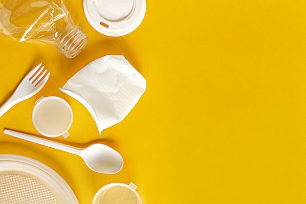 Choses en plastique brut secondaire pour le traitement ou le recyclage à plat sur fond jaune avec espace de copie