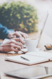 Choses pour le succès. gros plan d'un jeune homme travaillant sur un ordinateur portable et tenant la main sur une tasse de café alors qu'il était assis au café-terrasse