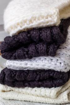 Choses tricotées pliées blanc et noir sur un fond en bois blanc