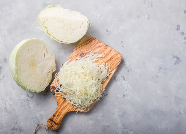 Chou bio frais haché sur une planche à découper en bois préparer pour la cuisson. vue de dessus