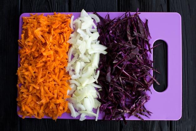 Chou bleu frais haché, oignon et carotte sur la planche à découper violette sur le fond en bois noir. vue de dessus.