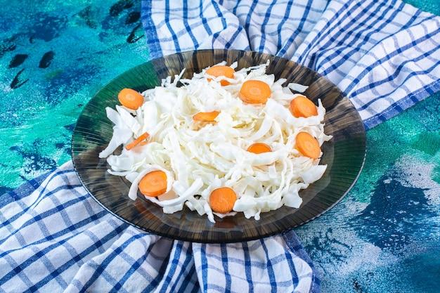 Chou et carottes tranchés dans une assiette sur un torchon