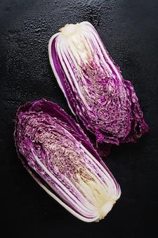 Chou chinois violet cru frais coupé en deux sur une vieille surface en béton noir. vue de dessus.