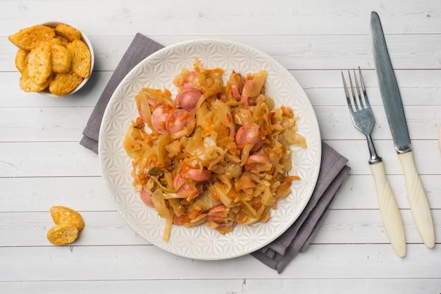 Chou cuit avec des saucisses dans une assiette sur la table.