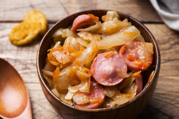 Chou cuit avec des saucisses dans des bols en bois sur la table.