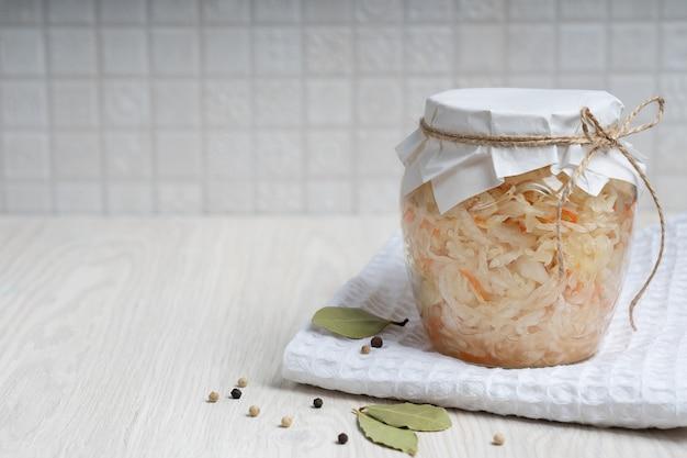 Chou fermenté dans un bocal en verre recouvert de papper artisanal sur serviette blanche sur table en bois