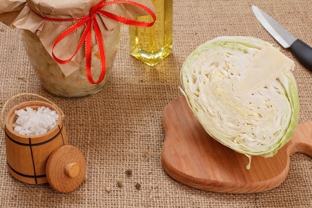 Chou fermenté fait maison avec carotte dans un bocal en verre, tête fraîche de chou, sel et bouteille d'huile sur le sac. salade végétalienne. le plat est riche en vitamine u. nourriture excellente pour une bonne santé.