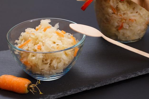 Chou fermenté fait maison avec carotte dans un bol en verre et peut, cuillère en bois sur fond noir. salade végétalienne. le plat est riche en vitamine u. aliments excellents pour une bonne santé.