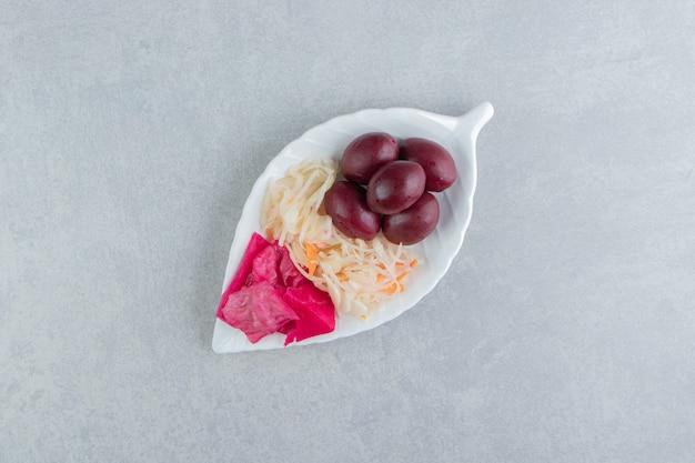 Chou fermenté et fruits sur plaque en forme de feuille.