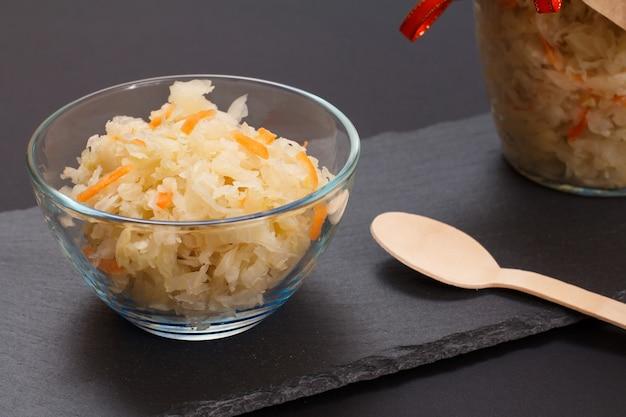 Chou fermenté maison avec carotte dans un bol en verre et peut sur fond noir. salade végétalienne dans un style rustique. le plat est riche en vitamine u. aliments excellents pour une bonne santé.