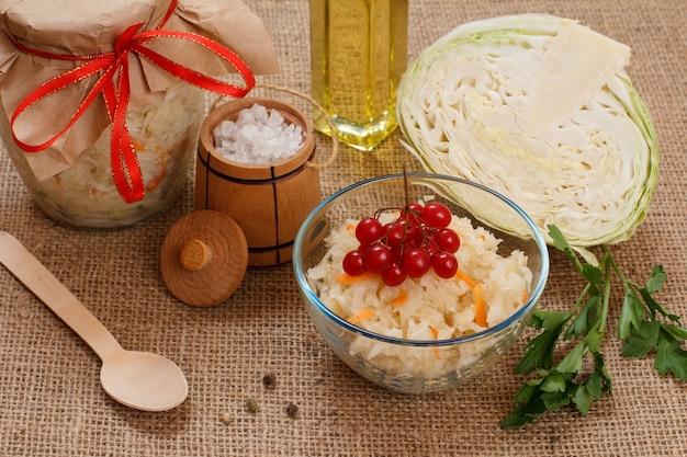 Chou fermenté maison avec carotte dans un bol en verre et peut, tête fraîche de chou, sel et bouteille d'huile sur le sac. salade végétalienne. le plat est riche en vitamine u. aliments excellents pour une bonne santé.