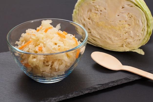 Chou fermenté maison avec carotte dans un bol en verre avec tête fraîche de chou sur fond noir. salade végétalienne dans un style rustique. le plat est riche en vitamine u. aliments excellents pour une bonne santé.