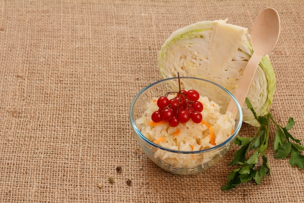 Chou fermenté maison avec carotte et grappe de viorne dans un bol en verre sur un sac. tête fraîche de chou sur le fond. salade végétalienne. le plat est riche en vitamine u. aliments excellents pour une bonne santé.