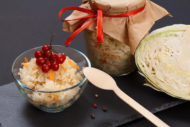 Chou fermenté maison avec carotte et grappe de viorne dans un bol en verre. tête fraîche de chou et boîte de verre sur le fond. salade végétalienne. le plat est riche en vitamine u. aliments excellents pour une bonne santé.