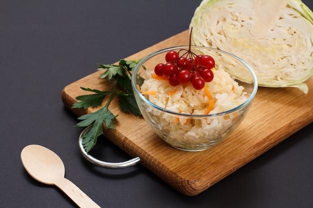 Chou fermenté maison avec carotte et grappe de viorne dans un bol en verre. tête fraîche de chou sur le fond. salade végétalienne. le plat est riche en vitamine u. aliments excellents pour une bonne santé.