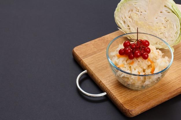 Chou fermenté maison avec carotte et grappe de viorne dans un bol en verre. tête fraîche de chou sur le fond. salade végétalienne. le plat est riche en vitamine u. nourriture excellente pour une bonne santé.
