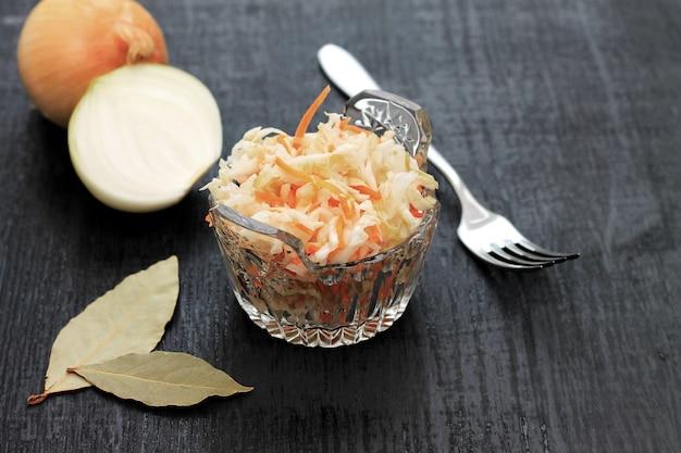 Chou fermenté. nourriture végétalienne. choucroute à la carotte et épices dans un bol sur le fond sombre. nourriture tendance.