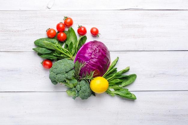 Chou-fleur, brocoli, chou bleu, citron et tomates cerises sur un fond en bois blanc. nourriture de menu de fond