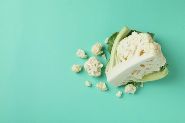 Chou-fleur juteux frais avec des tranches sur fond de menthe