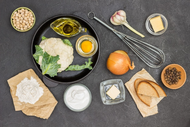 Chou-fleur, oeuf cassé et huile d'olive dans une poêle. fouetter, beurre, ail, pois chiches et pain sur la table. fond noir. mise à plat