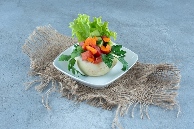 Chou-fleur sous les feuilles de persil, laitue et légumes hachés sur un plateau sur une table en marbre.