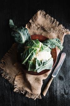 Chou-fleur sur une toile de jute et un couteau