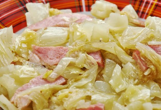 Chou frit du sud - style campagnard cuit. le chou est frit avec de l'oignon et du bacon dans ce plat d'accompagnement simple et rapide.
