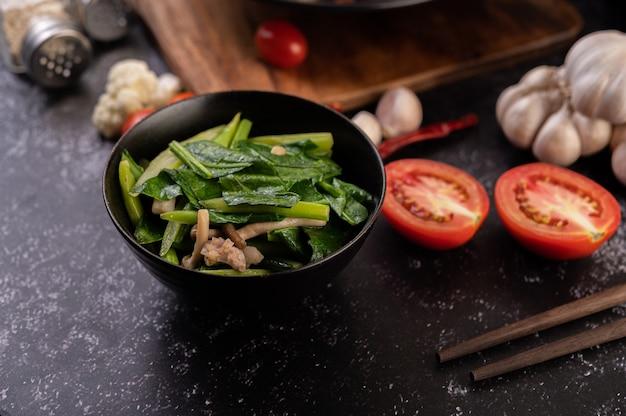 Chou frit et poitrine de porc sautés dans une assiette posée sur une assiette en bois.