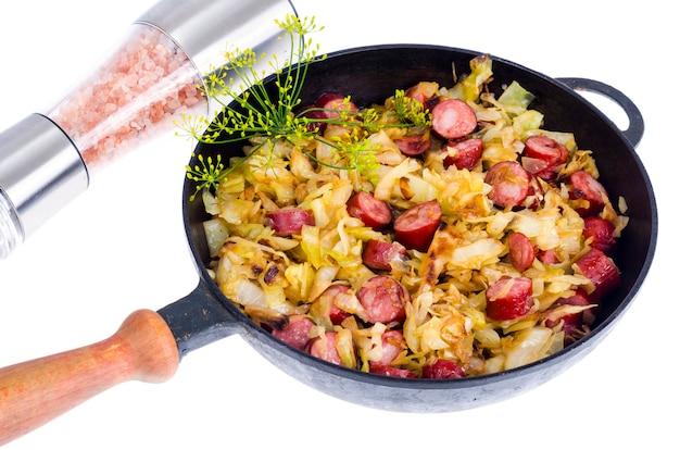 Chou frit avec des saucisses fumées dans une casserole