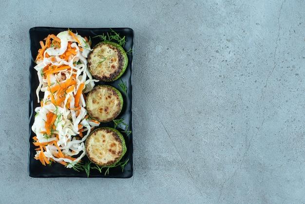 Chou haché et carottes au poivre grillé sur plaque noire.